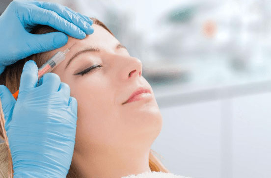 Woman receiving dermal filler injection in forehead